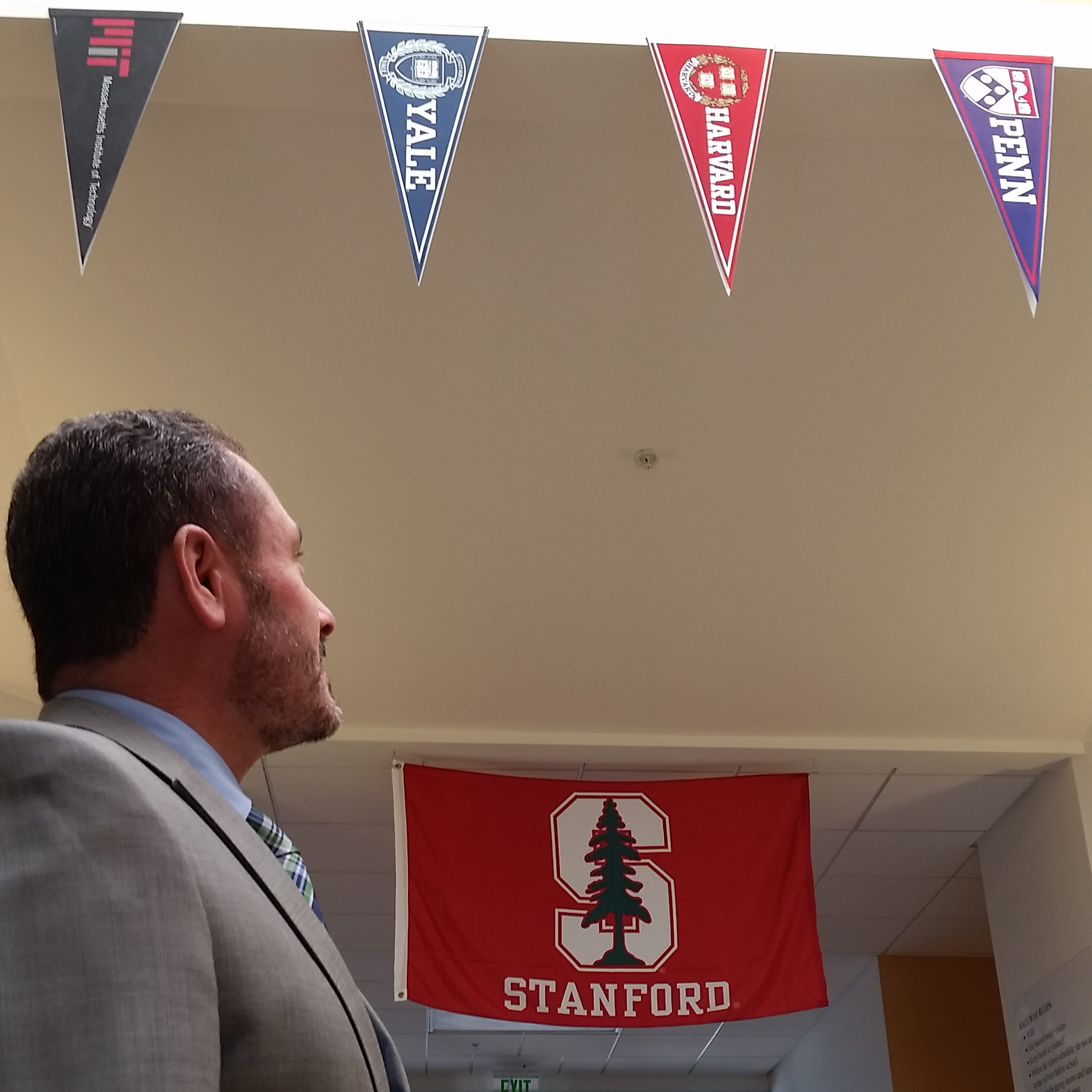 Guillermo Morales '94 looks at the college pendants hanging in the hallway of Thomas Jefferson Elementary School (San Leandro, Calif.).