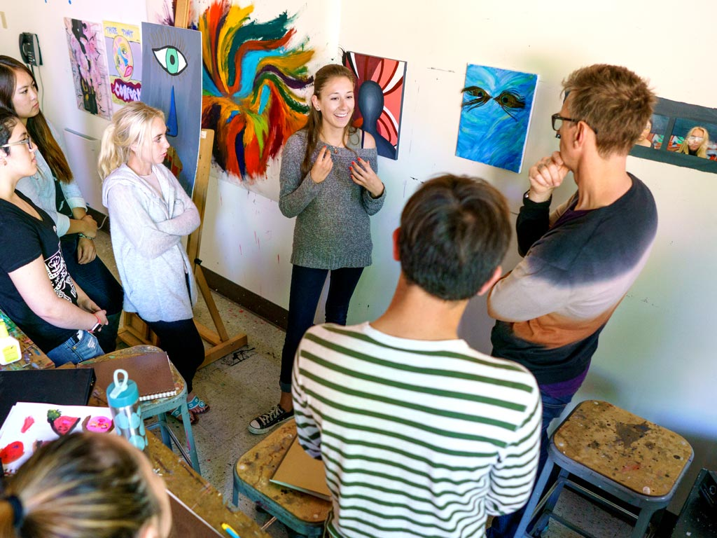 Students in art class critiquing a painting.