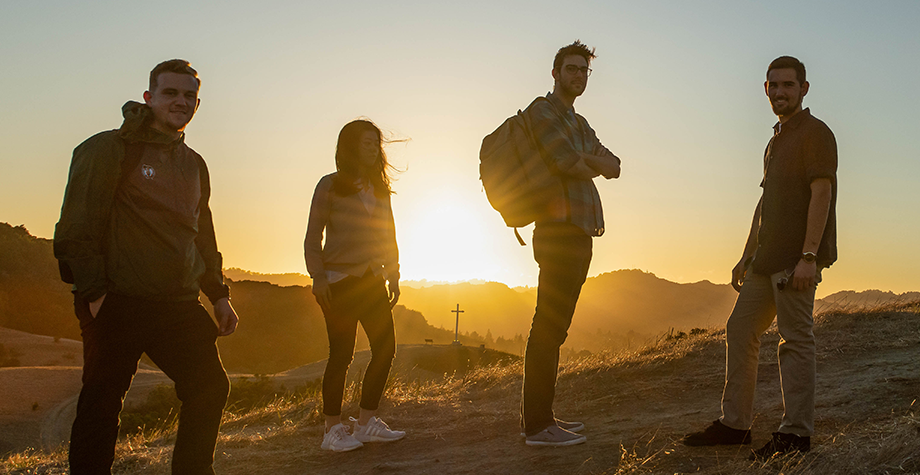 Four students stand on a hill with the sunsetting behind them.