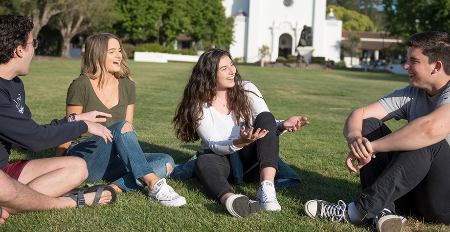 4 students sit on the lawn in front of the chapel