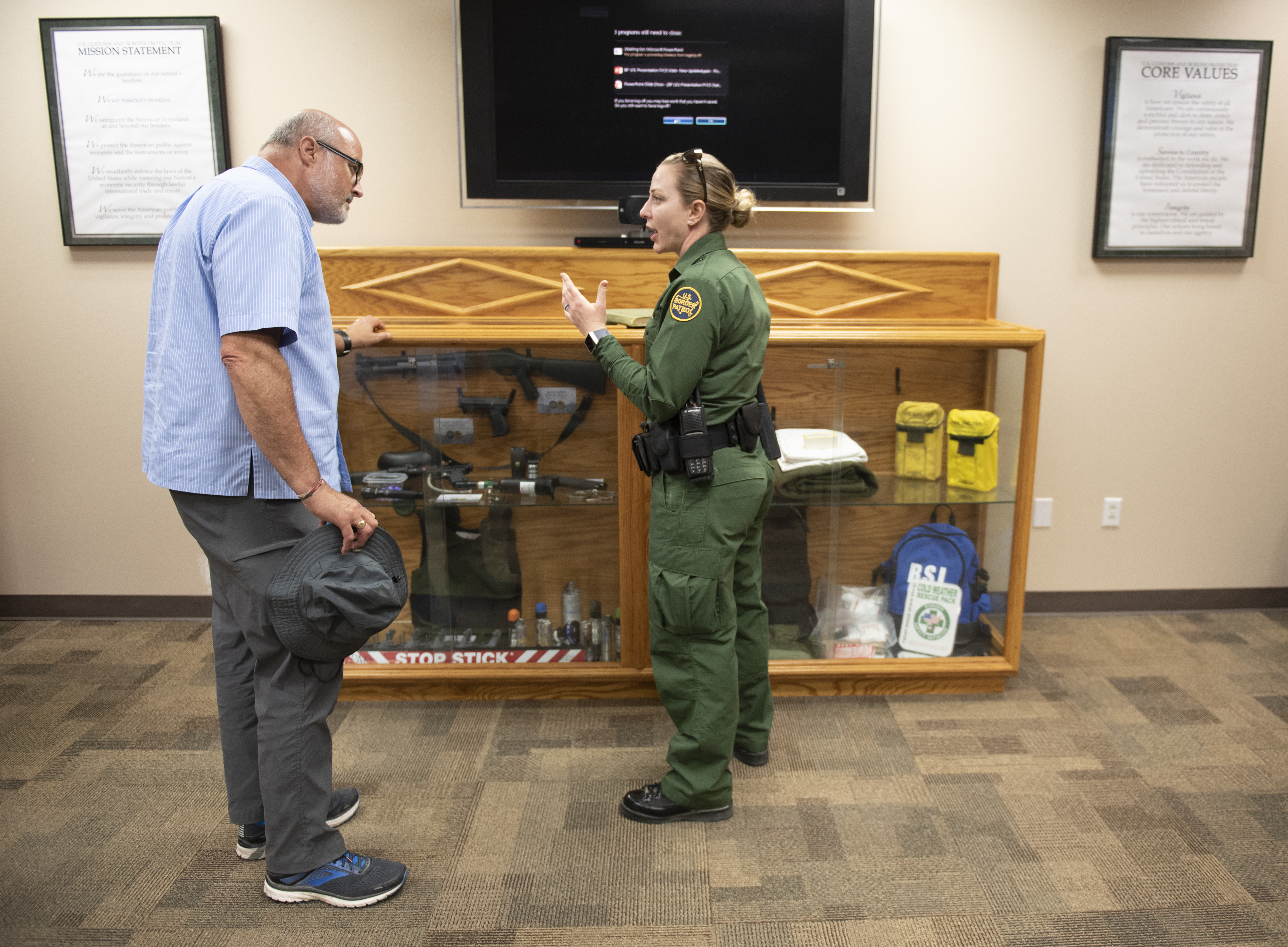 Professor Norrie Palmer learns about the tools used by Border Patrol Officers from Agent Renteria at the Border Patrol San Diego Sector Headquarters.