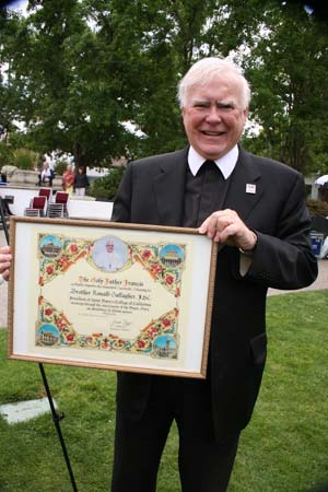 Brother Ron holds a framed blessing from Pope Francis