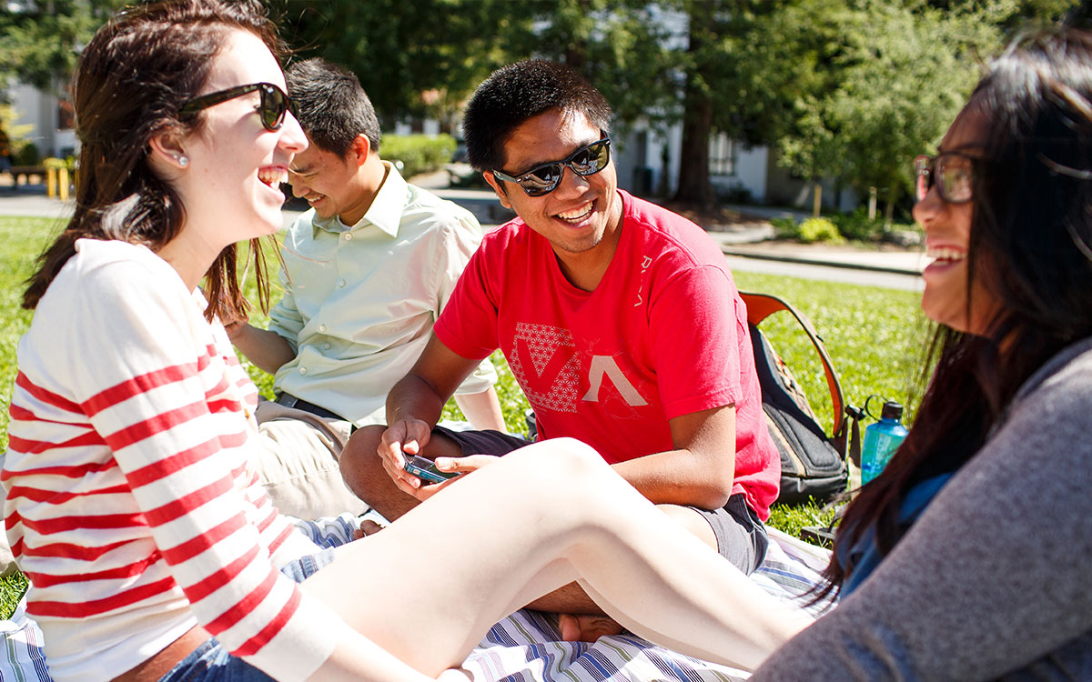 A group of students sit on the Chapel lawn and talk.