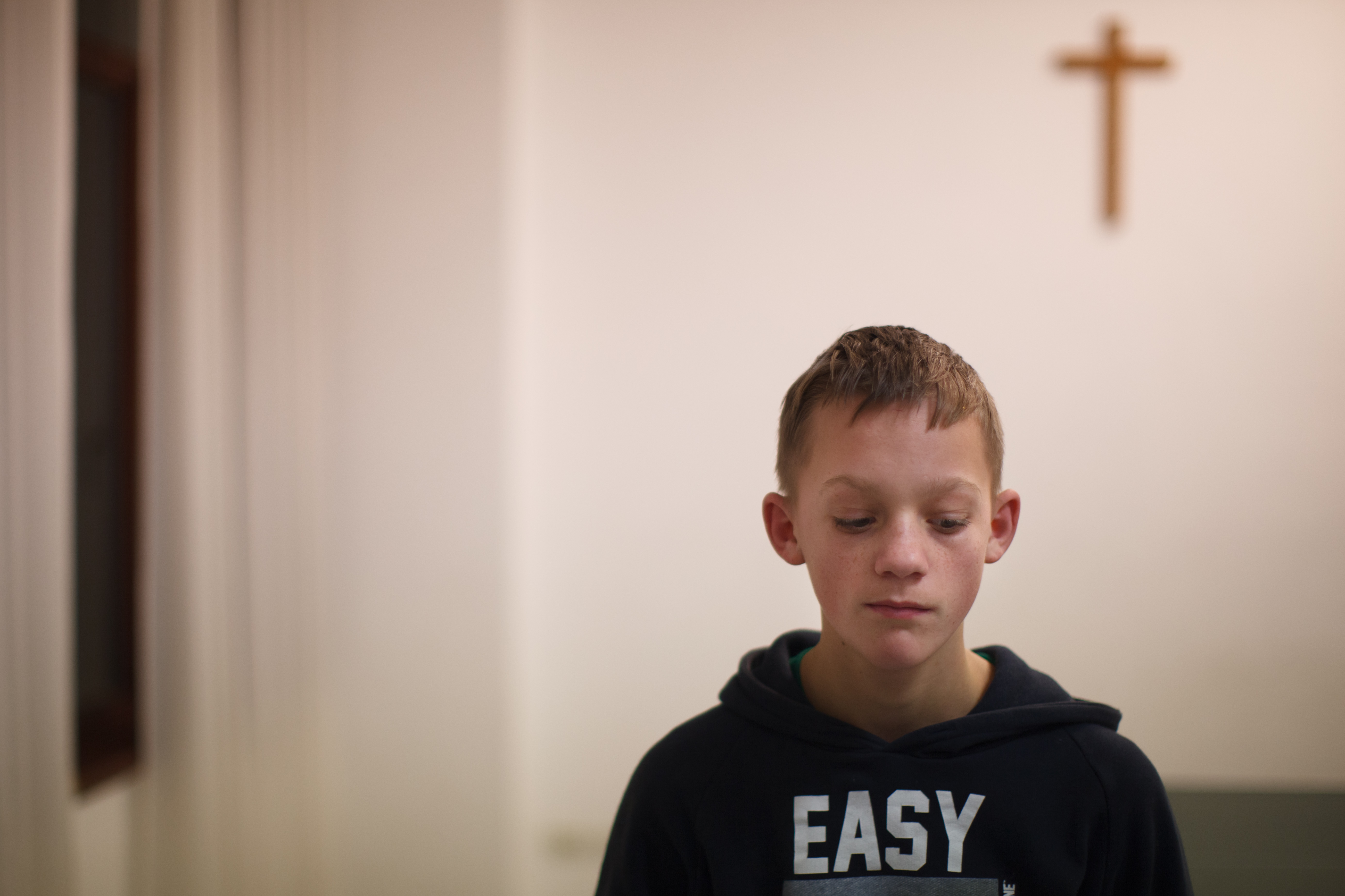 Daniel reflects in front of the cross in a room used for evening prayer