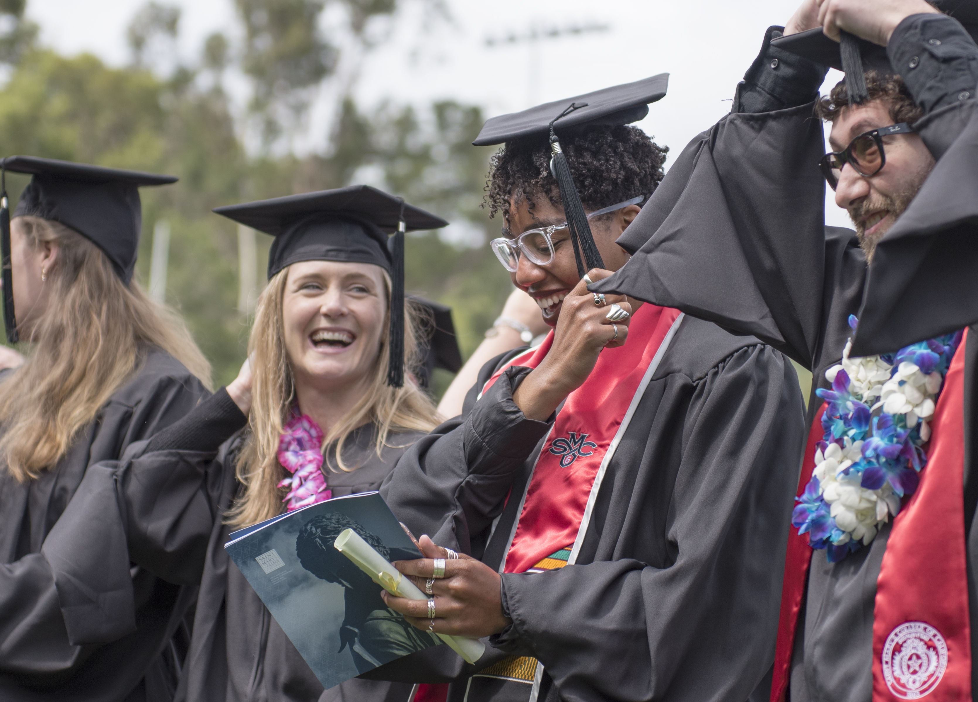 Candidates for diplomas at the 2019 Graduate and Professional Studies Commencement celebrate their achievements with laughter.