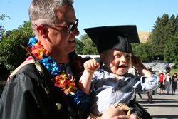 Grad's baby tries on graduation cap