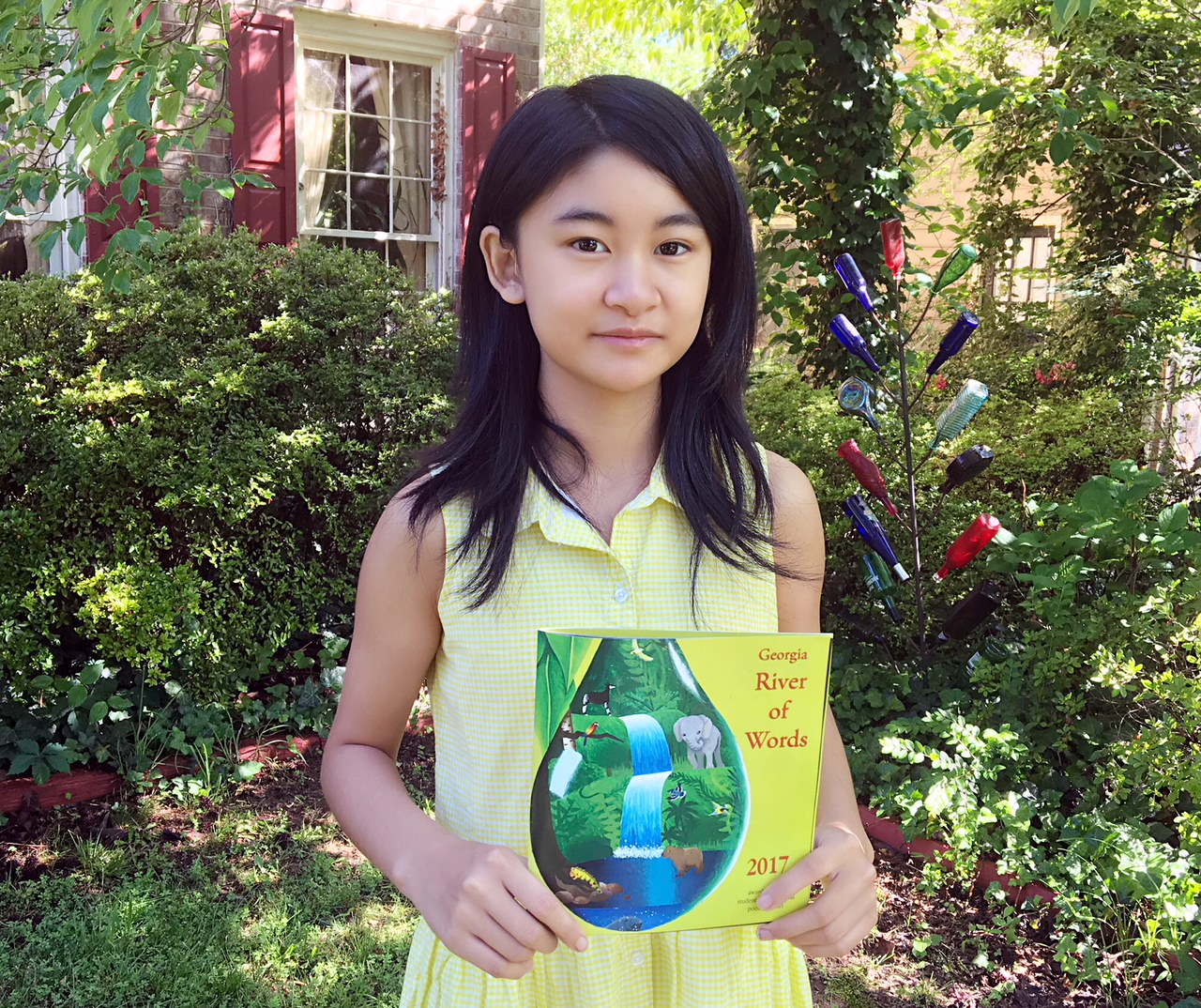 Nicole Li, a 14 year old student, stands outside, in front of a window and a row of large bushes. In her hands at waist level, she holds the Georgia River of Words 2017 anthology.