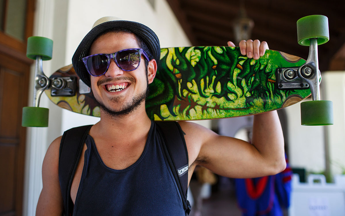 A Saint Mary's student smiles with his skateboard over his shoulder in the Arcade.