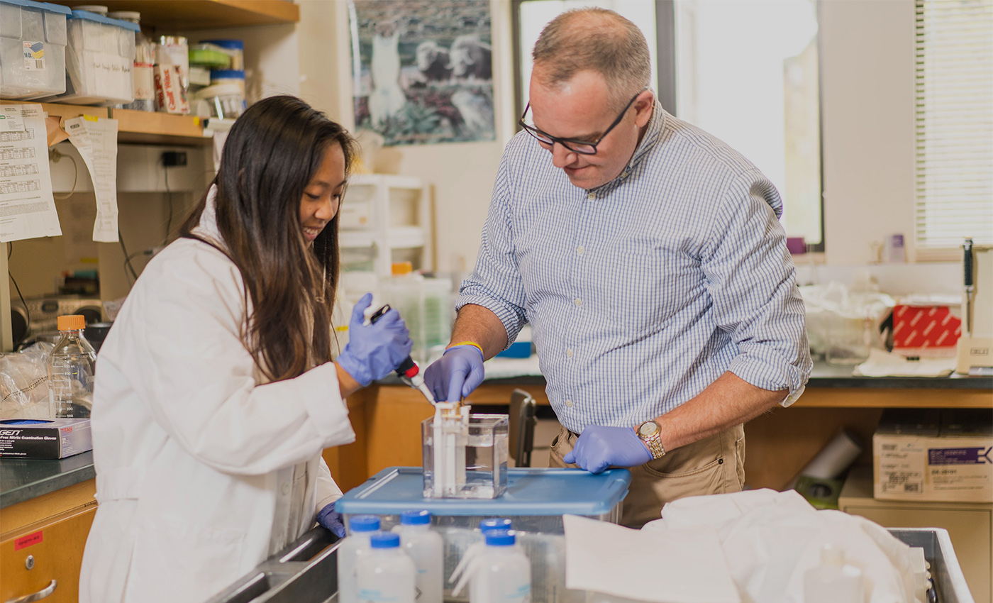 Professor Keith Garrison works with a student in the lab at Saint Mary's.