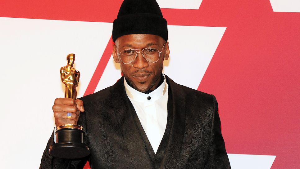 Mahershal Ali holding gold trophy.
