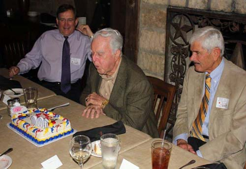 Clay McElroy blows out candles on a 100th birthday cake during a celebration in Texas, as Gary Luquette, president of Chevron North America, and Vic Revenko, president of the Chevron Retirees Association urge him on.