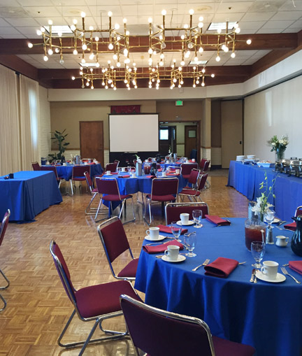 Orinda Room set-up for an event with a screen and banquet tables to the side.