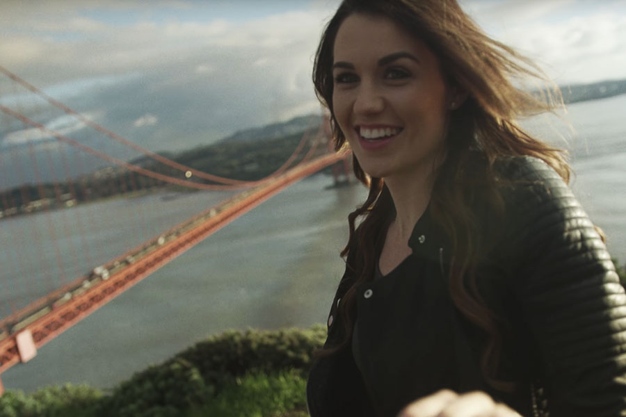Rachel Fletcher MA '17 stands in front of the Golden Gate Bridge during filming of the Saint Mary's institutional commercial.