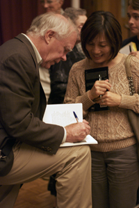 Hass signs a copy of his book after the event.