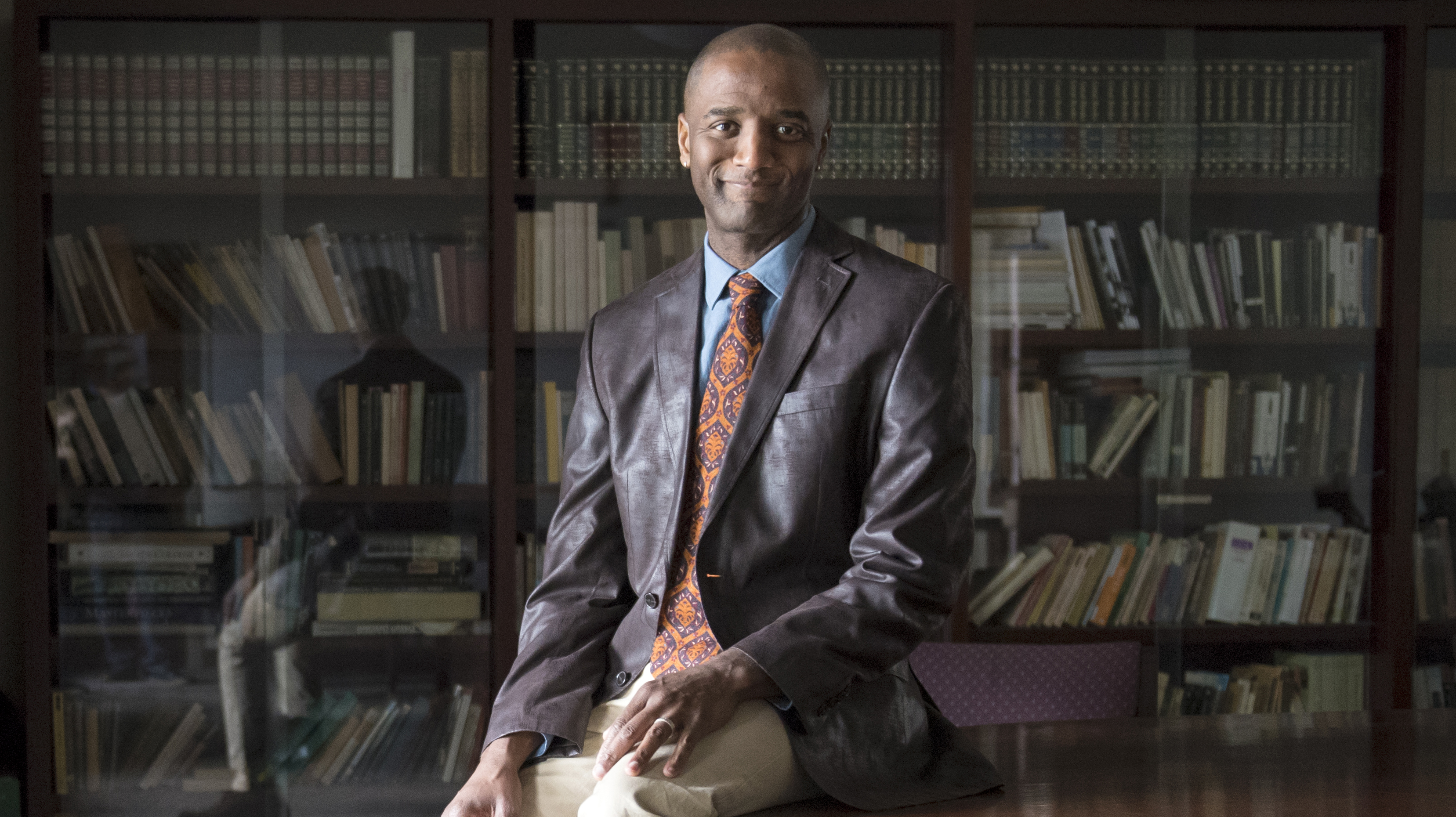 S. Marshall Perry, associate professor in the Kalmanovitz School of Education sitting on a table with books behind him.