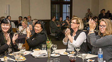 Faculty celebrate their colleagues, including Jennifer Heung, second from left, at the 2015 Scholars Reception.