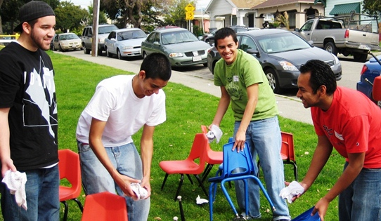 Students clean chairs at a local preschool.