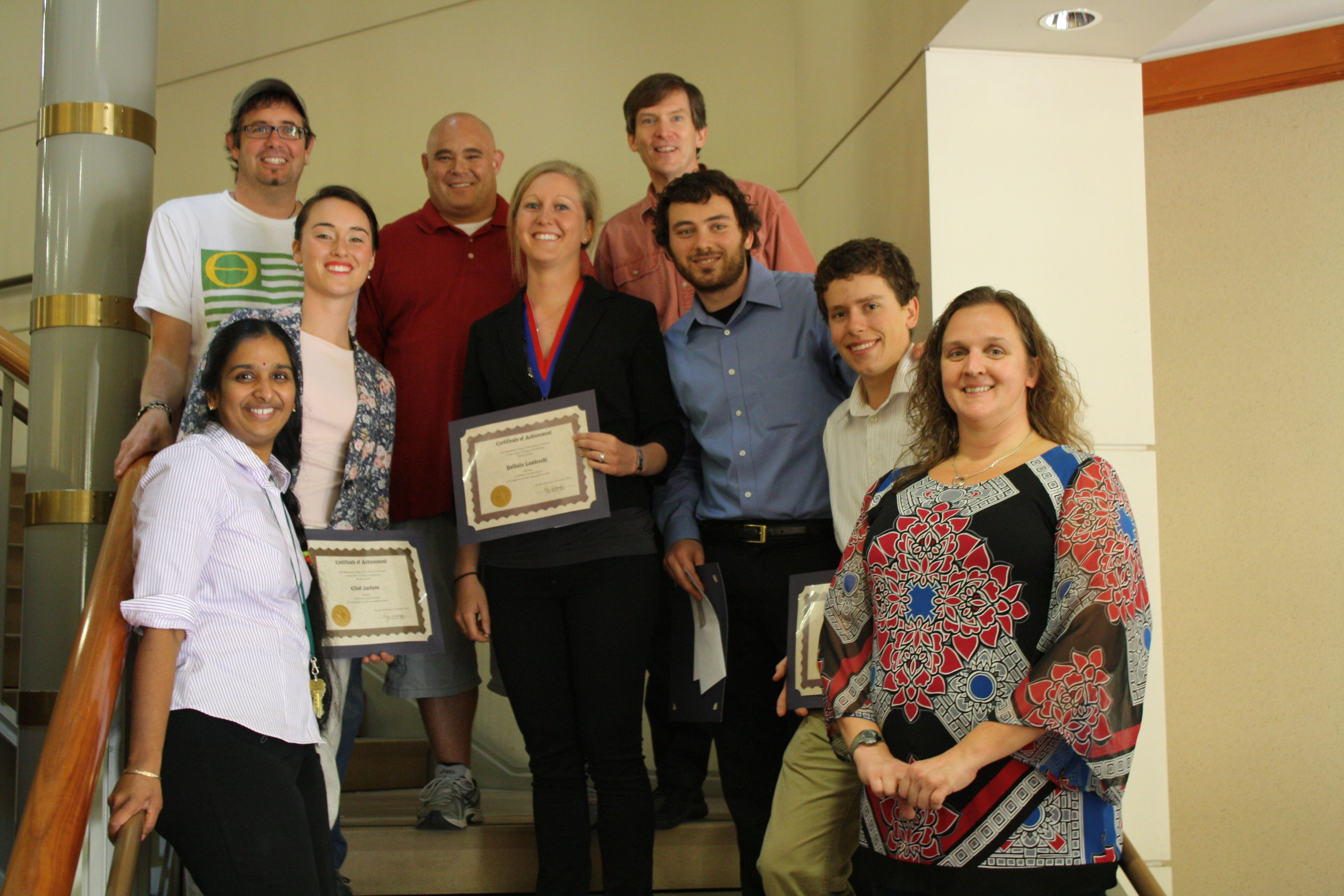 Students with projects chosen as superior by a panel of faculty and students were: Eliot Jackson, Nathalie Lambrecht, Anthony Villafranca, and Vincent O'Brien (pictured in the center, left to right). On the periphery of the photo are the faculty mentors: Dr. Vidya Chandrasekaran, Dr. Michael Marchetti, Dr. Jeff Bernard, Dr. Joel Burley, and Dr. Valerie Burke.
