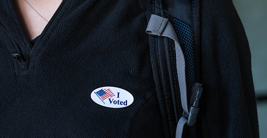 student in sweater with an I Voted sticker