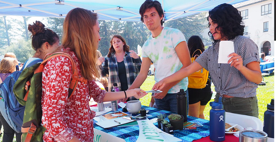students gather at a booth