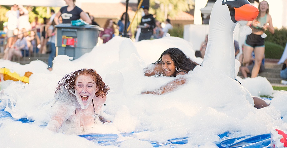 2 students slide down a slip in slide covered in bubbles