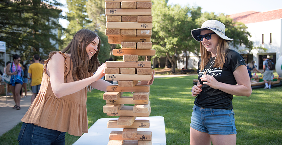 2 students play a giant game of jenga out on the lawn.