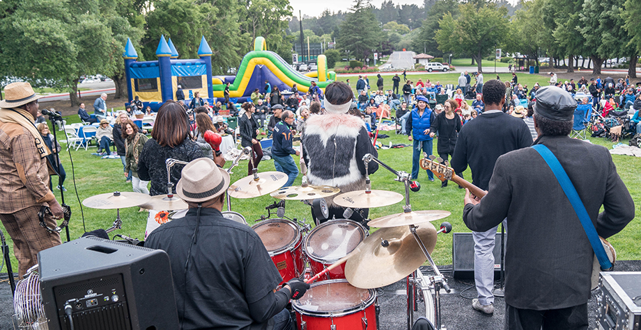 A band plays to a crowd during Music on the Lawn