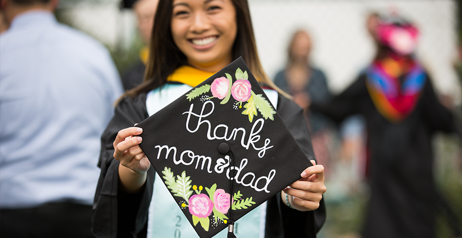 "student holds their graduation cap, which they decorated to say ""thanks mom & dad"""