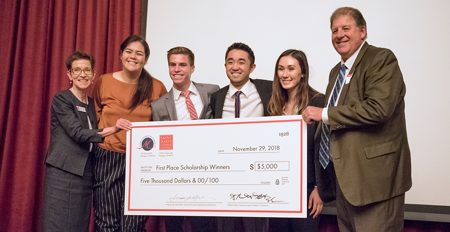 Winning student team stands with their scholarship