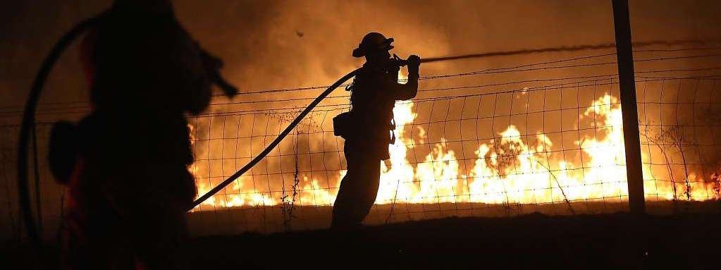 MARIPOSA, CA - JULY 18: A firefighter sprays water on the Detwiler Fire on July 18, 2017 in Mariposa, California. More than 1,400 firefighters are battling the Detwiler Fire that has burned more than 25,000 acres, forced hundreds to evacuate and destroyed at least 8 structures. The fire is five percent contained.