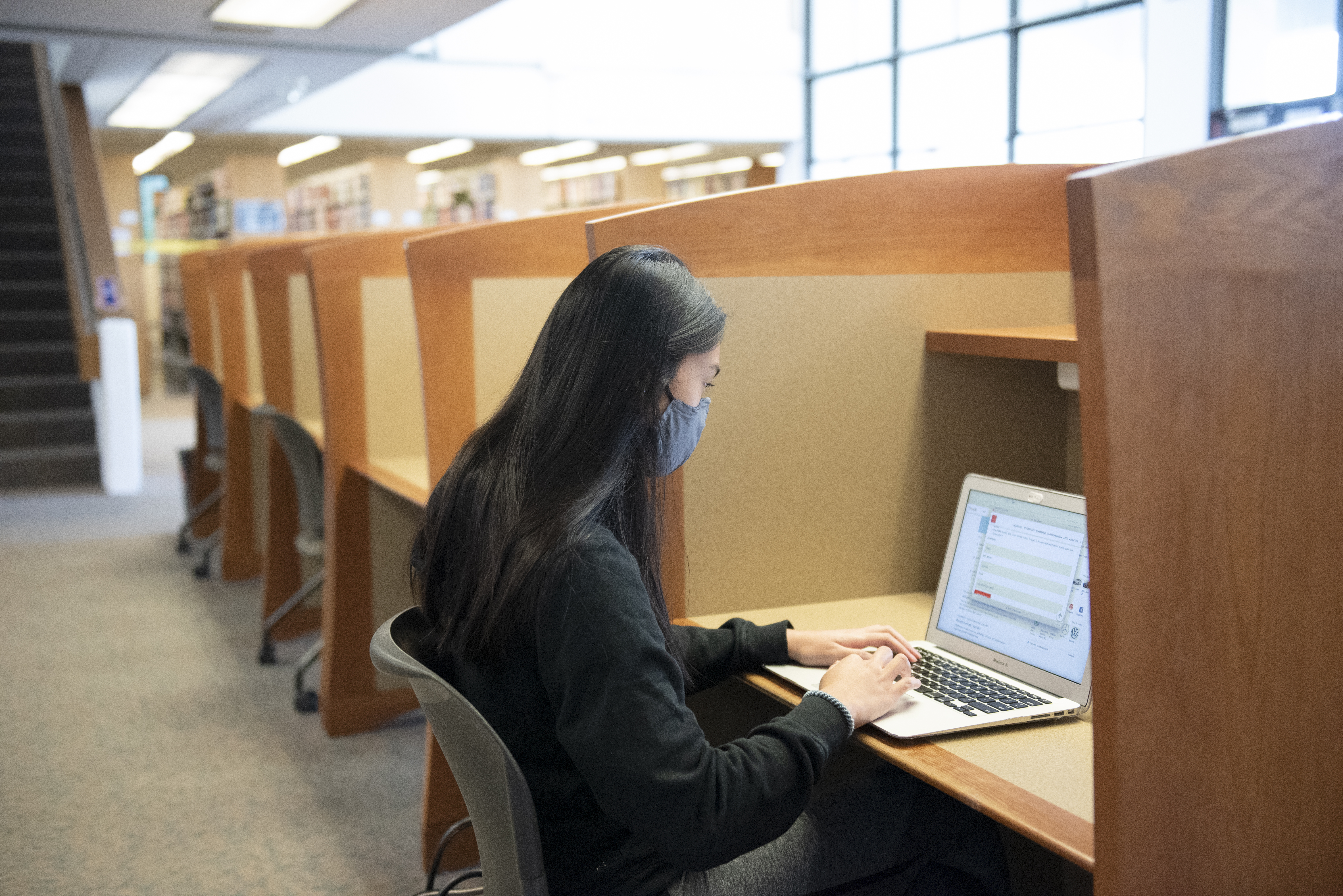 Student works on their laptop in a library carrel with mask on