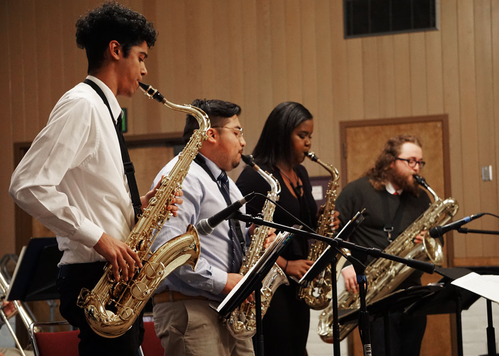 Four saxophone players performing
