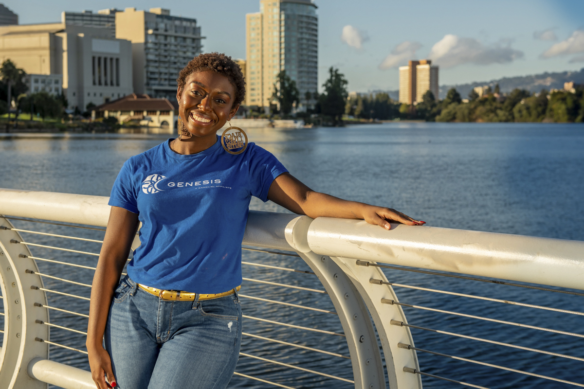 Student in her work shirt standing on a bridge in front of water smiling