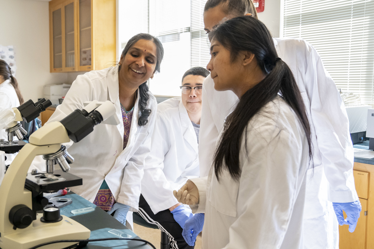A professor smiling while showing students something through a microscope