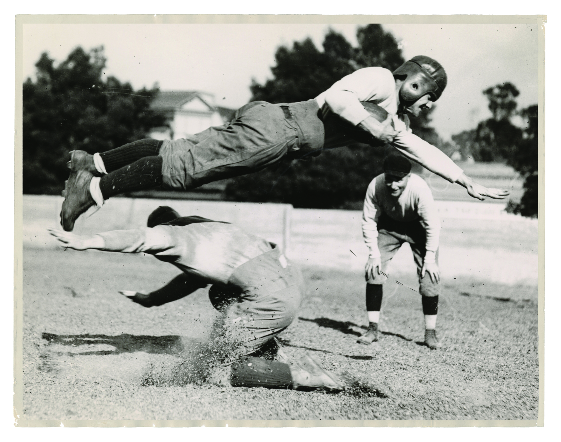 A Saint Mary's Football player goes airborne as Madigan looks on in this 1930s publicity photo.
