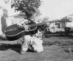 Brother Donald as a child playing the guitar