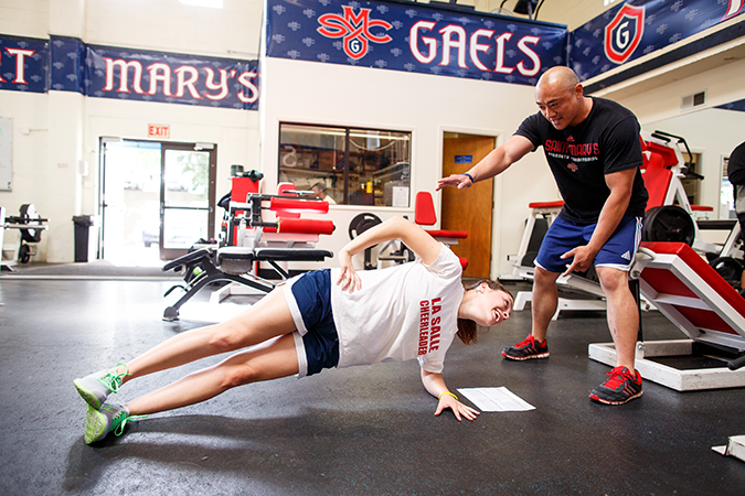 Alumnus Andre Tameta coaching a student athlete during a strength and conditioning internship