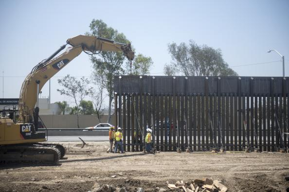 Construction workers install a new stretch of primary border wall between San Diego and Tijuana.