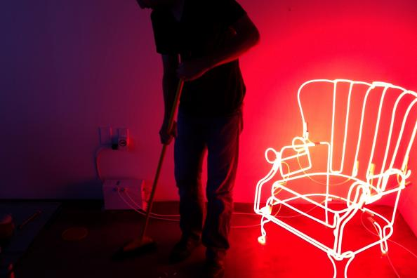 Johnson sweeping in his studio with neon chair
