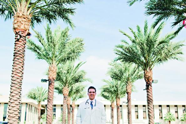 Eduardo Garza '91 stands in front of a medical center.