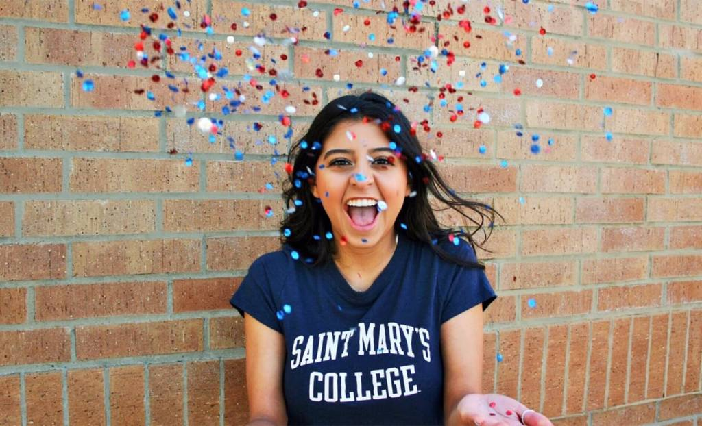 An admitted student throws confetti in front of a brick wall wearing a Saint Mary's College t-shirt.