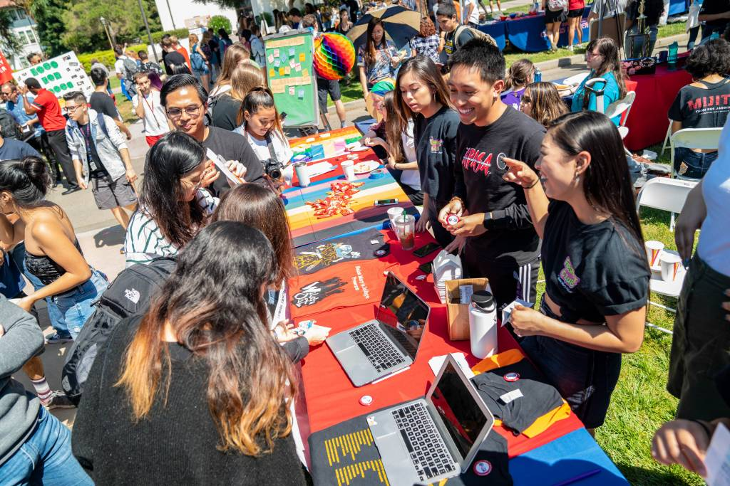Saint Mary's students laugh and talk at a long table during one of the involvement fairs.