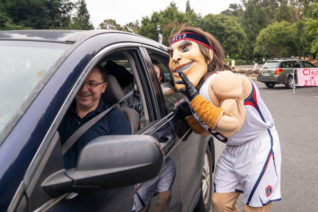 Mascot talking to a parent through a car window