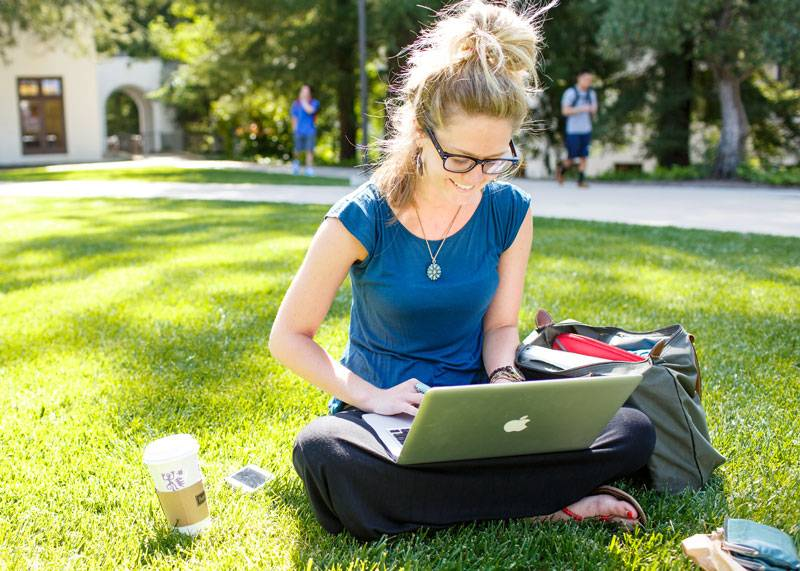 A student smiling while sitting on the grass and working on her computer