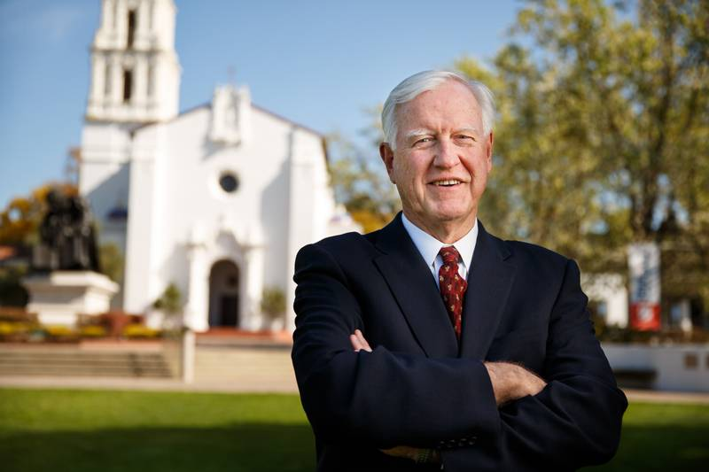 Saint mary's President standing with arms crossed in front of the chapel