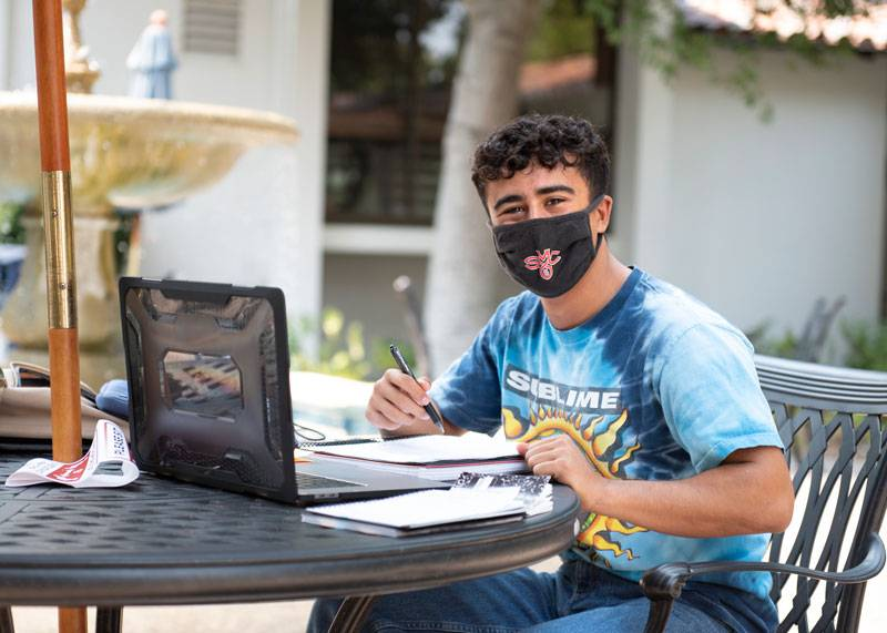 A student with his mask on sitting outside working on his computer.