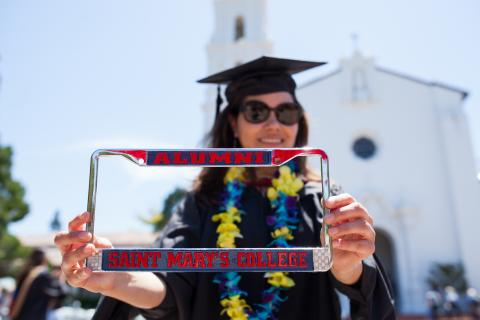 student standing in front of the chapel in her regalia holding her alumni license plate