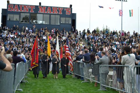 2018 Commencement Flag Bearers with bleachers in background