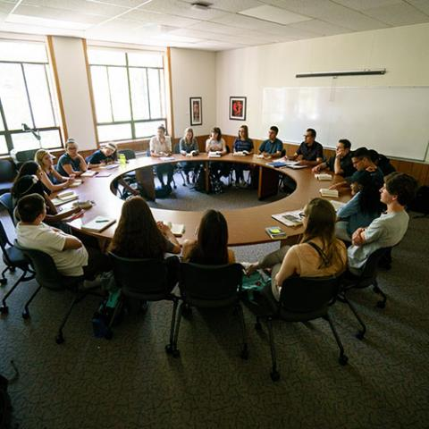 Students sit around a circular Seminar table.