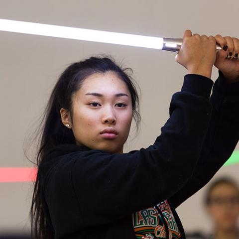 A girl holds a light saber during a Jan Term class.